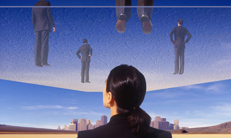 Businesswoman looking at glass ceiling